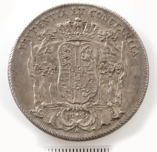 Adv. Kongen på tronen under tronhimmel.  Rev. Riksvåpen i kronet skjold, som holdes av to villmenn.