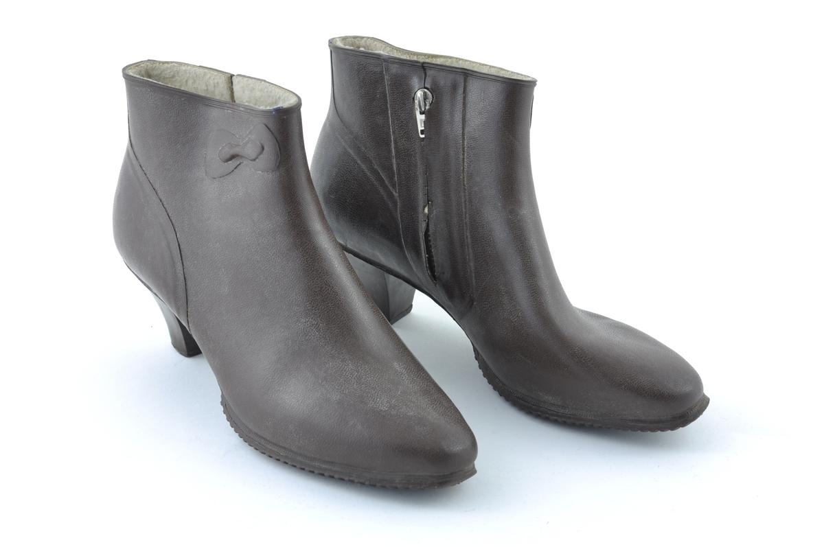 Ett par damestøvletter av gummi. Foret med ullstoff. Glidelås på innsiden. Halvhøy hæl, litt spiss tå.