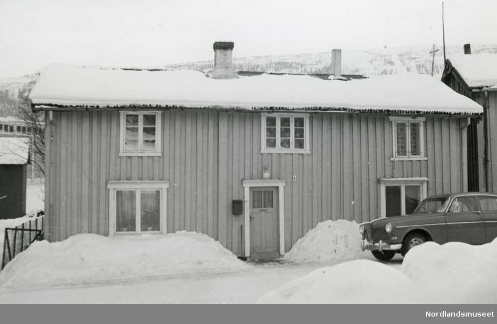 """Bygning, Kaigata 4. Langveggen. Trepanel. Bil utenfor. Snø. 2 etasjer med stående trepanel. Et par sprossede vinduer i 2. etg. Ved døren en postkasse og nummeret """"4"""". En rund lys- kuppel overdøren. På taket 2 piper hvor den ene er et tynt rør. En bil står utenfor til høyre. Hagegjerde til venstre. Litt av noen bygninger på begge sider. Eier/beboer? Ragnar Aaberg."""