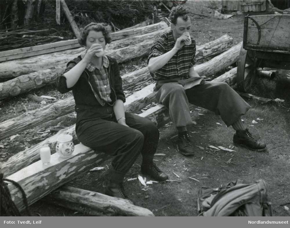 En mann og en dame sitter på en stokk og drikker melk.