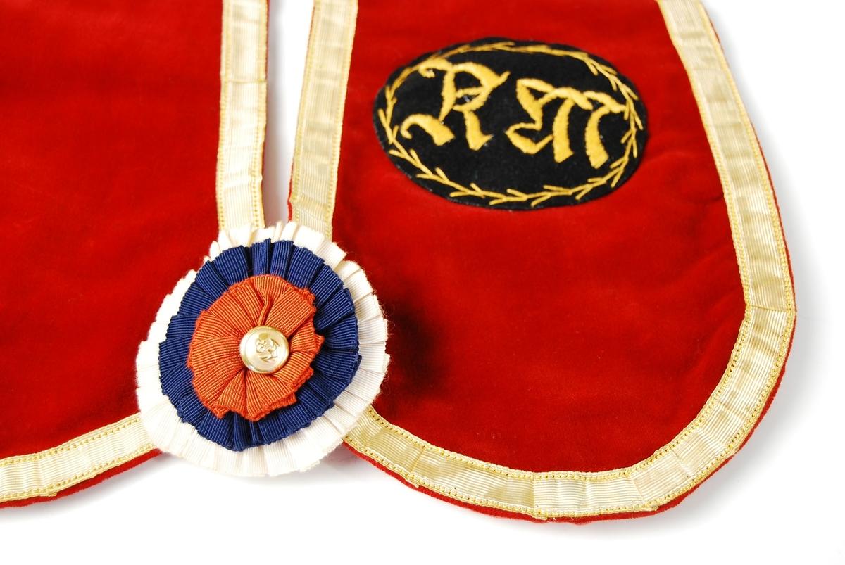 """Regalie av burgunderrødt fløyelsstoff. Stivt, gullfarget pyntebånd langs kant. Bakstykket er av pudderrosa bomullsstoff.  Dekorert med tøyrosett nederst, som forbinder høyre og venstre side av regaliet. Tøyrosetten har rød, hvit og blå farge og gullknapp i midten. Gullknappen har ankermotiv.   På høyre side av regaliet er det påsydd et ovalt merke - svart med brodert kantdekor og bokstavene """"KM"""" i midten. Brodert med gul tråd."""