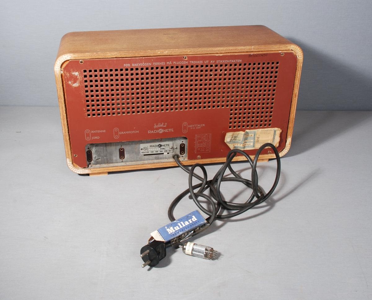 Radiomottaker for kort-/mellom- og langbølgemottak. Rektangulær kasse med åpning for høyttaler dekket av tekstil på framsiden. Ved siden av stasjonsvelger med viser på skala. Knapper for regulering av lydstyrke, lysstyrke, søk og valg av frekvensbånd/grammofon. På baksiden kontakt for antenne, jord og grammofon. Merkelapp for betalt stempelavgift, og skilt med wattstyrke. Tegning av kretskort. Til ledningen er festet en eske med Mullard radiorør. Kabel med støpsel på baksiden