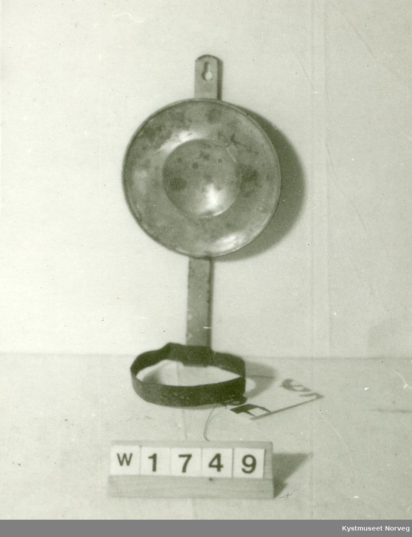 Holderen består av et enkelt veggoppheng med en tynn blikkring til å holde brenneren. En rund messingreflektor, skålformet.