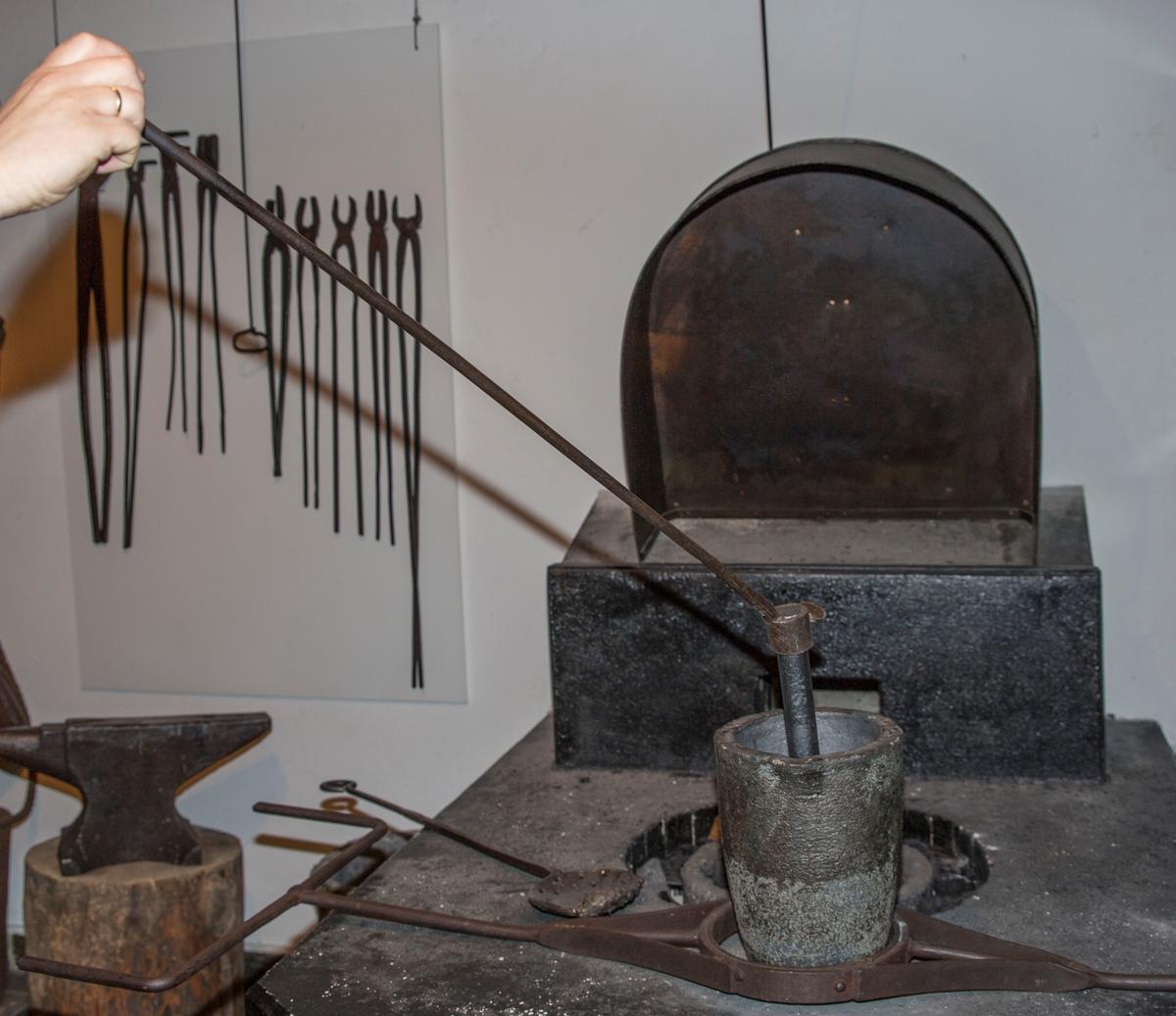 Rett stålskaft med en rund krok i den ene enden. I den andre enden har skaftet en ring som er tredd rundt enden av en grafittstav.