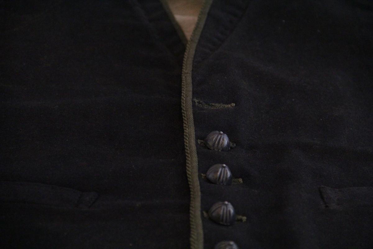 Vest i mørkebrunt ullstoff i forstykket, grovt linstoff på baksiden, ubleket. For i ubleket grovt stoff på forstykket. Lengre foran enn bak. En lomme på hver side. Knapperad på venstre side, to flere knapper enn det er knappehull til, dekorknapper. Påsydd kantebånd i grønt på forstykket.