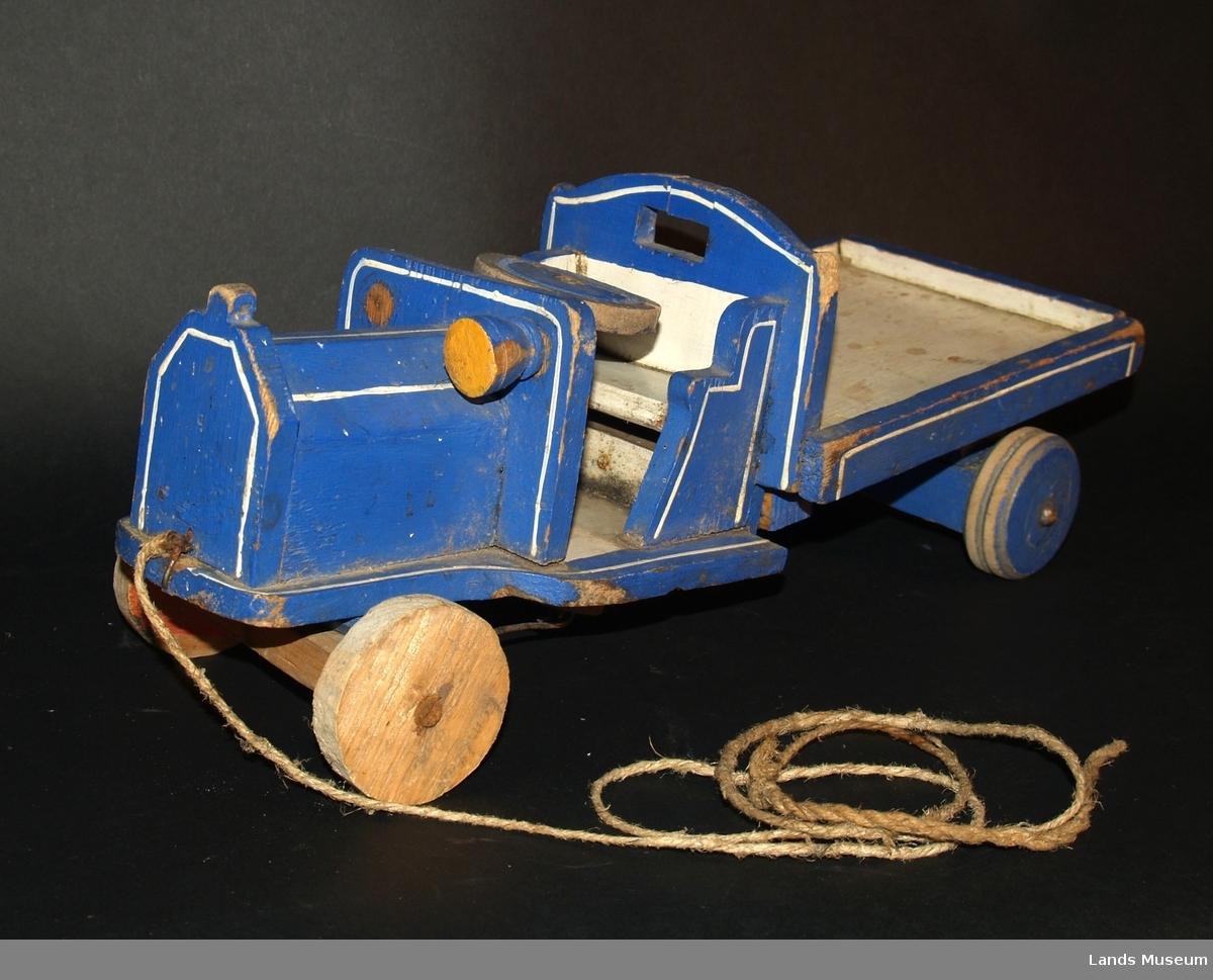 """Lekebil av tre, blåmalt med kvit pyntekant. Åpen""""modell"""" med trehjul og lasteplan. Treratt. Heimelaga.  Mangler ei frontlykt."""
