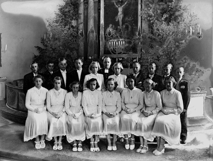 Konfirmander, tio flickor, åtta pojkar och pastor Henriksson.Interiör av Stora Mellösa kyrka.