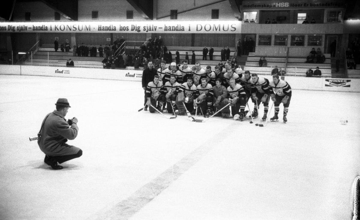 Ishockey klar 31 januari 1966Ett ishockeylag i idrottskläder samt med ishockeyklubbor i händerna står uppställda på isen för att bli fotograferade. En fotograf med kamera sitter framför dem på isen. Publik står på läktaren och betraktar det hela.