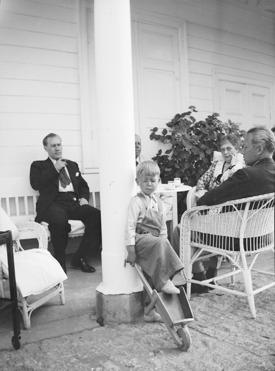 Fra venstre: Iacob Ihlen Mathiesen, statsråd Christian Pierre Mathiesen, et barnebarn, Marie Gleditsch og Haaken Christian Mathiesen sitter i svalgangen på Linderud Gård.