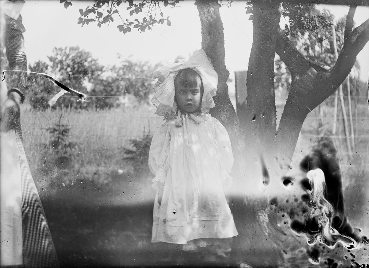 Et barn står under et tre og ser mot fotografen. Barnet har på seg en stor, flott kyse. Vi se armen og skjørtet til en voksen kvinne som sikkert er sammen med barnet.