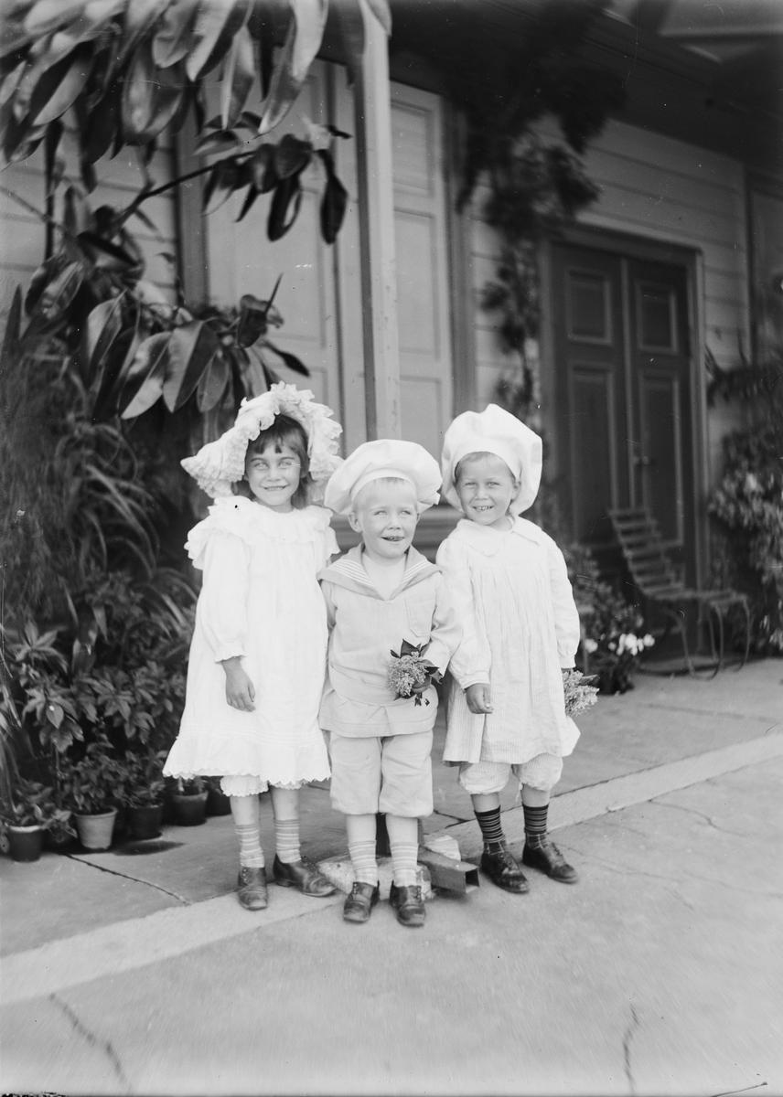 Tre barn står under svalgangen til hovedhuset på Linderud Gård. De ser glade ut og holder små blomstebuketter i hendene.