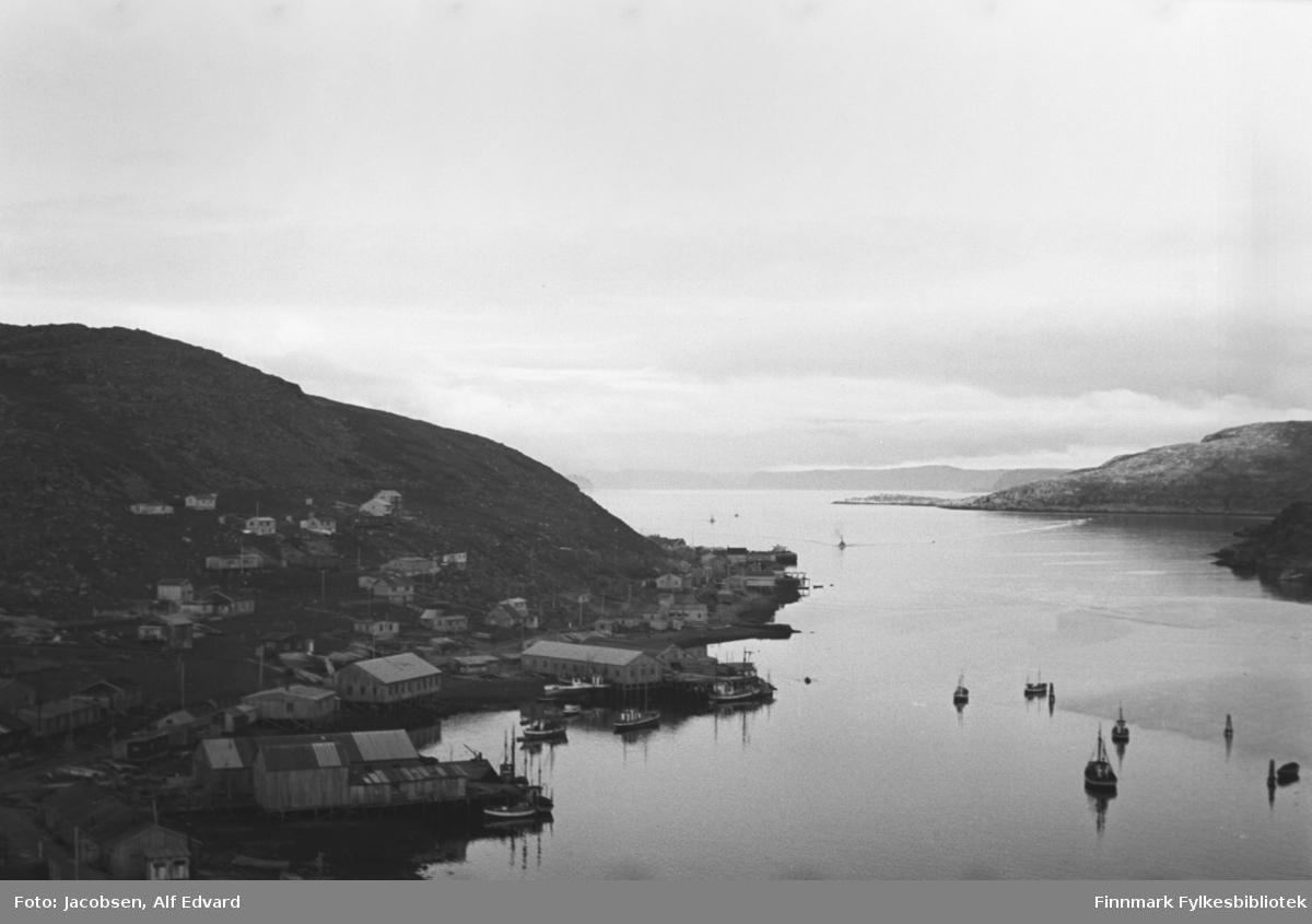Havøysund sett litt ovenfra med Havøya på venstre side av bildet. I det blikkstille Havøysundet ligger flere båter, også inne i havna ligger flere båter fortøyd og noen ved kai. Den store brakke nede til venstre på bildet er fiskebruket til Samvirkelaget. I strandkanten litt lenger bort ligger brakka til Alma Thomassen. De to brakkene innerst i havna er Coop-brakka nærmest kamera og den litt større brakka ved siden av er Harald Olsens snekkerverksted. Den avlange brakka som ligger på en kai som stikker ganske langt ut i havna er Anton Olsens materialhandel, etterhvert omgjort til fiskemottak. Endel hus er bygd i lia ovenfor havna og på neset midt på bildet. Til høyre på bildet er fastlandet og neset oppe, midt på bildet, er Trollfjordneset. Noe diffust i bakgrunnen ligger et fjellparti som er Måsøya.