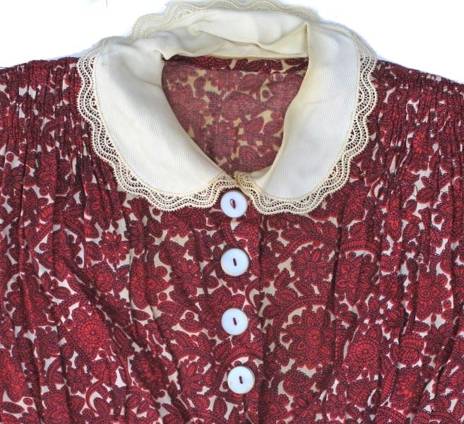 Kjole med lange ermer av rødmønstret bomullstøy. Hvit blondekrage. Trykknappknepping i brystet, med hvite pynteknapper. Puter på skuldrene. Trolig hjemmesydd.