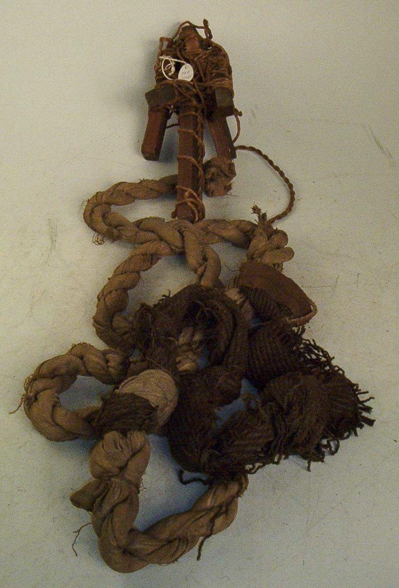 Tau med krok. Kroken er laget av deler fra en krakk som er surret sammen med en tråd slik at den har fått en dregglignende form med fire mothaker rundt en stamme. Til dreggens stamme er det bundet et ca. 260 cm langt tau som er flettet sammen av strimler fra et istykkerrevet ullteppe.