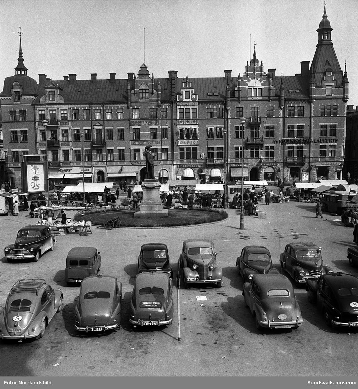 Stora torget med marknadsstånd och parkerade bilar.