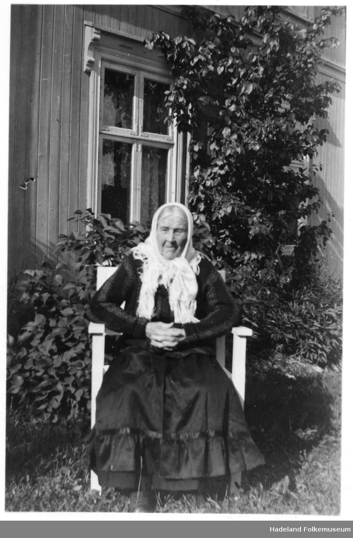 Gammel kone sittende i hagen, bilde 1 i stasklær og på bilde to med en katt på fanget. Syverine Flødsveen.