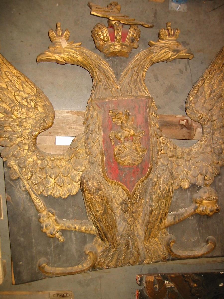 Akterspegelsornament. Ryska tsar- (kejsar-?)dömets vapen: krönt, förgylld dubbelörn med röd sköld, varpå är fästad en skulptur av St. Göran och draken. Sjöfynd, restaurerat och kompletterat.