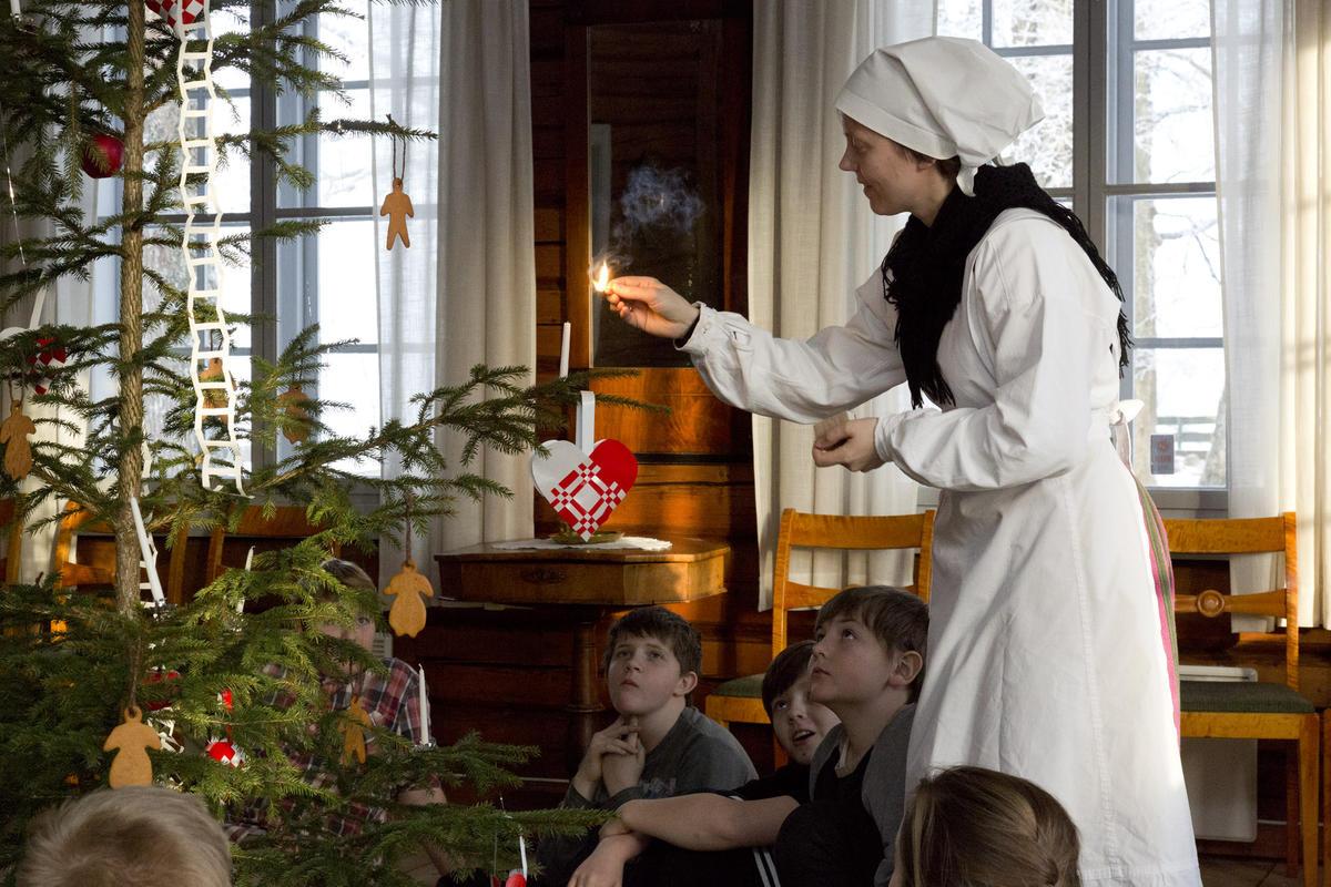 Tjenestejenta anno 1880 tenner et stearinlys på juletreet.