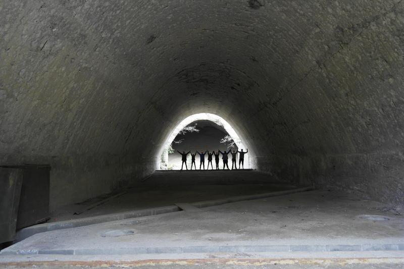 8 elever står i enden av et tunnel. De holder hverandre i hånden