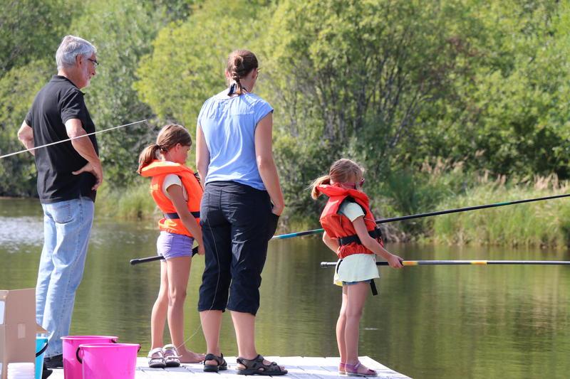 Foto av en familie som står og fisker