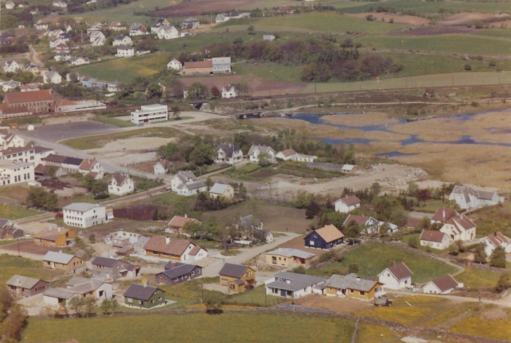 Utsyn over Bryne mot nordvest. Rossaland i framgrunnen. Bryne mek. i venstre kant. Telebygget i framkant av jernbanelina som deler bildet. Rett bak ligg garden til Eilef A. Bryne, Bryne bruk 1/2.