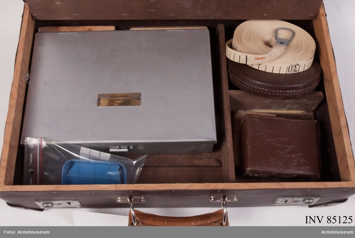 Portfölj av märket UNICA, Mariestad, av papp innehållande i den övre delen mot locket i blanketthållaren:  Skisspapper 2 st blyertspennor 1 st kautschuk, Pencil Rubber 1 st tomt kuvert 1 st öppnat kuvert med små etiketter 1 st 30 cm linjal  Mittsektionens verktygssats: 1 st skruvmejsel, större 1 st stämjärn 1 st hammare, mindre, med universalverktyg, Bahco 1 st tång 1 st skruvmejsel, mindre 1 st sticksåg, Viking Extra märkt SKA 1 st förstoringsglas 1 st ficklampa 1 st måttband stål ihoprullat, 2 meter  Nedre sektion, under luckan: Fingeravtrycksutrustning m/1943 innehållande argentorat, DM-pulver och blyvitt pulver i aluminiumburkar, pensel i aluminiumrör, 1 st blå plastlock i påse, trasigt 1 st ask plastilin, valsmassa och lykopodium 1 st måttband i tyg, 10-25 meter 1 st pincett 1 st sax Gummivals Satskort KAIF april 1954
