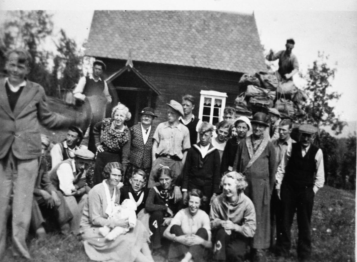 Bilde av en liten gruppe av mennesker. Kvinner, menn og barn. Alle er avbildet foran et hus.