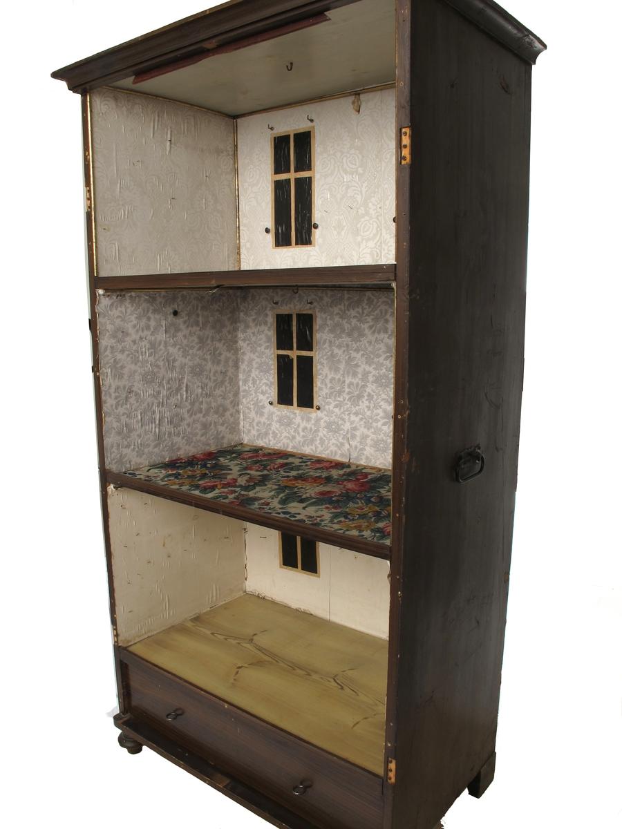 Dukkehus med møbler og utstyr. Furu, nøttetresmalt. Papirtapet. Høyt todørs skap med fylling i hver dør, ådret, nøkkelskilt i blikk, sorte jernhanker i sidene.  På høyre side ringeapparat. Lav gesimslist. Kulebein i forkant.  Innvendig tre hyller = tre etasjer, skuff nederst.  Gulbrune, ådrete gulv.   Øverste etasje grått og hvitt stormønstret tapet,  1930-årene, 2 vinduer i sort glanspapir med lysere omramning, kroker for gardinopphenging, og hamrede smijerns gardinholdere. Tynne gull-lister rundt taket.  Tv.lysbryter.  Innlagt lys, ant. fra 1930-årene.  Midtrommet:  Tapet med grå blomster på hvit bunn med rosa striper, messing gardinholdere.  2 vinduer som over.  Bryter utv. i taket.  Hjørne-hengelampe med firkantet pergamentskjerm, 1920-årene som tapet.  Nederst:  Kjøkken med hvite vegger, 2 vinduer, 2 kjegleformede lampeskjermer 1930-årene.  Veggfast tallerkenhylle, ringeapparat.