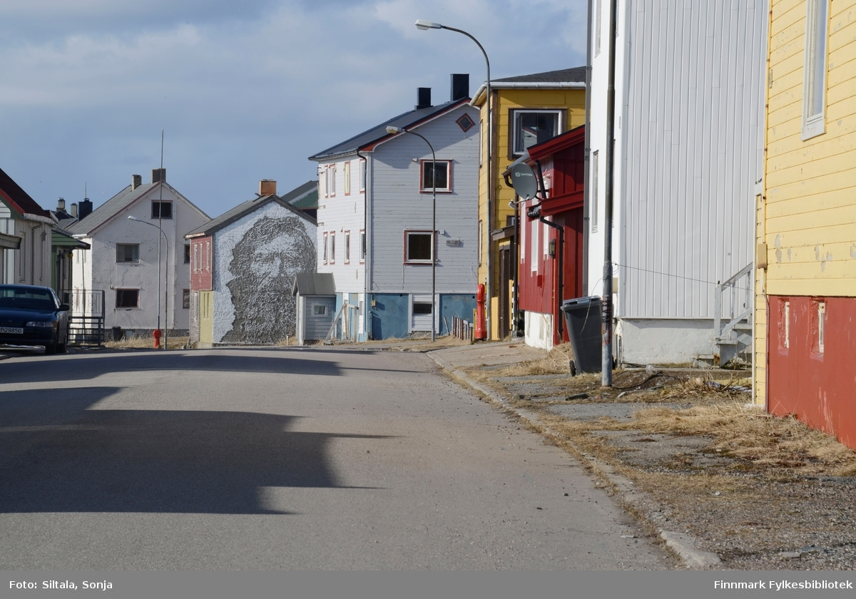 Fra Kristian 4 gate i Vardø i april 2015. Man kan se gatekunst, som er en del av et kunstprosjekt av kunstneren Pøbel. Han ønsket å sette oppmerksomhet på forfall, fraflytting og lokalhistorie med kunst som metode. I 2012 inviterte han 13 internasjonalt anerkjente kunstnere til å utsmykke 55 vegger i Vardø by.