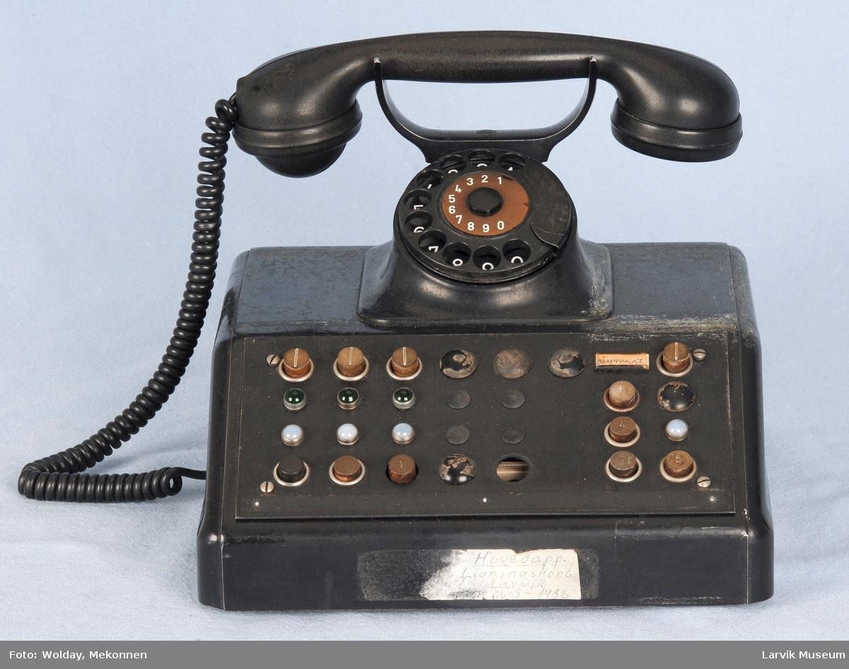 Kasse med telefon og tallskive øverst. Valgknapper i skråpanel. Lysfelt.
