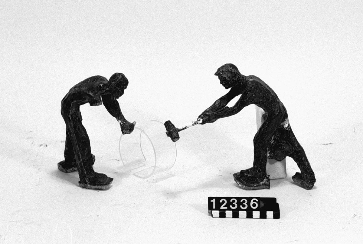 """Gipsmodell av skulpturgrupp, """"Hjulsmide"""", motiv från tillverkning av järnvägshjul samt avgjutning i brons av gipsmodellen. Bottendiameter: 460 mm. Största höjd: 350 mm."""