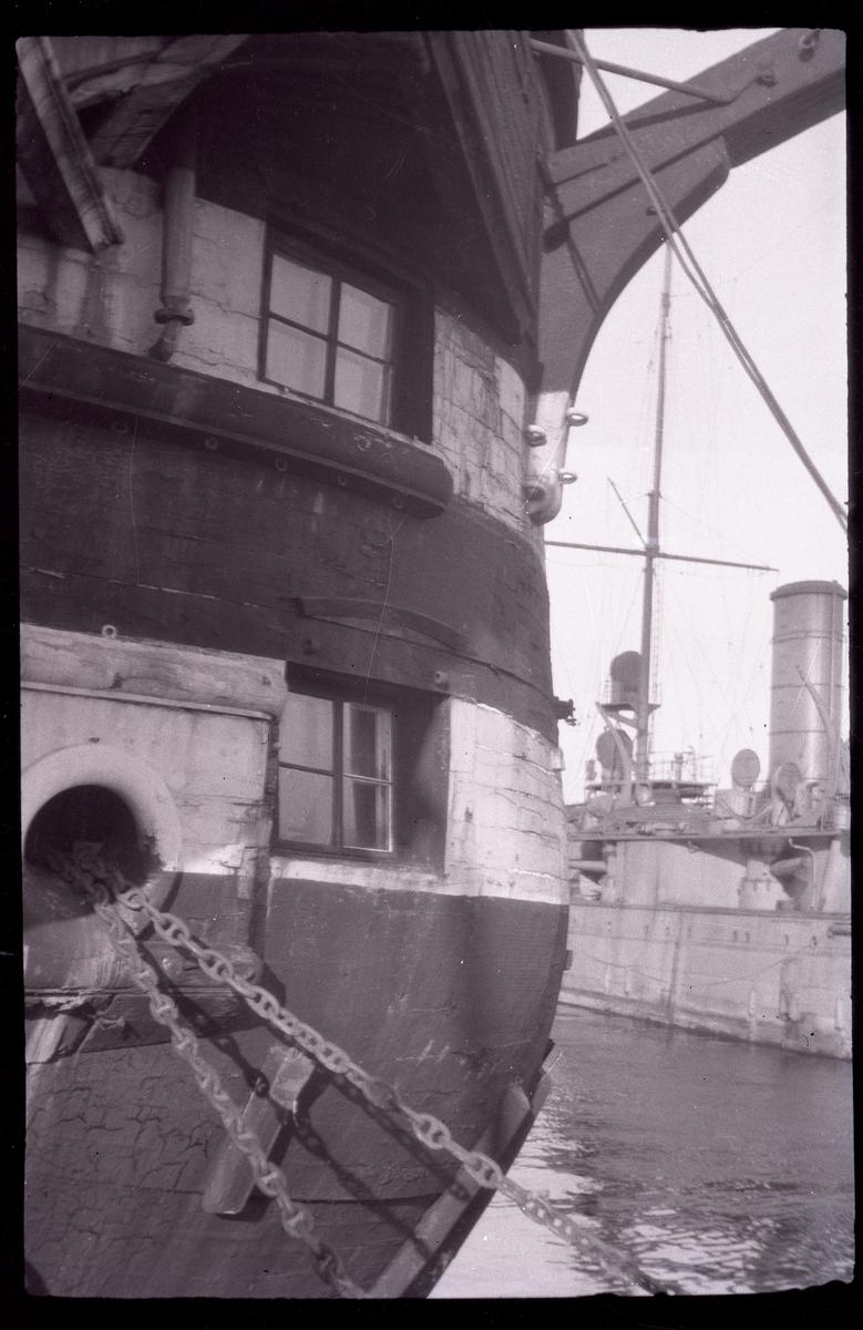 Bilden visar babords sida av linjeskeppets Stockholms bog. Fartyget är ombyggt till logementsfartyg, så att styckporter har blivit till fönster. Högst upp ser man vänstra kranbalken, i undre delen ankarkedjan. I bakgrunden ligger pansarskepp Dristigheten.