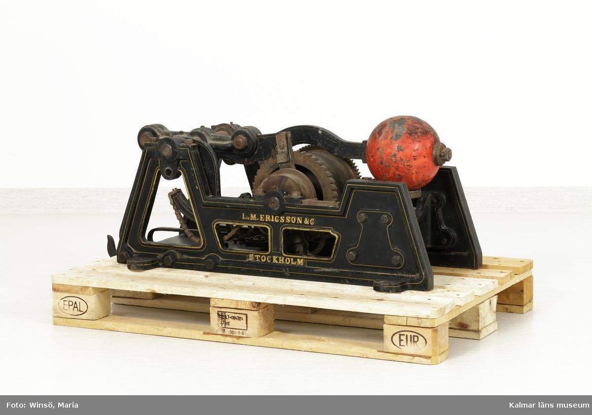KLM 8522:1-4. Klämtmaskin, med vikter. Fyra delar. Användes för att klämta i klocka vid brand. Klämtmaskin (:1) av metall; järn, stål och mässing. Ramen är målad svart med guldfärgade dekorlinjer. På ena sidan är tillverkarens namn gjutet i järnet: L.M. ERICSSON & C STOCKHOLM. Maskinen dras upp för hand genom en vev som sitter på ena sidan, handtaget saknas. Vid uppdragningen vevas en vajer runt kugghjulet. I ena änden av maskinen en platta med detaljer av mässing där elektricitet kopplades in. Genom att trycka på en knapp startades maskinen elektriskt och mekaniken drog igång så att den orangefärgade kläppen slog upp i klockan. Enligt L.M Ericssons produktktalog från år 1889 kunde maskinen ge ca. 80 klämtslag på en uppdragning.   Till maskinen hör två vikter med tillhörande viktskivor. Den största vikten (:2) med tillhörande viktskivor (:2:1-6) hängde i en krok vid maskinens ena kortände. Den andra vikten (:3), som är försedd med en fjädring, hängde i vajerns ena ände och kunde justeras med tillhörande viktskivor (:3:1-10). Till maskinen hör också en talja med väggställning (:4), som vajern gick genom. Alla lösa delar till maskinen är av järn och är målade med en blank, svart färg.