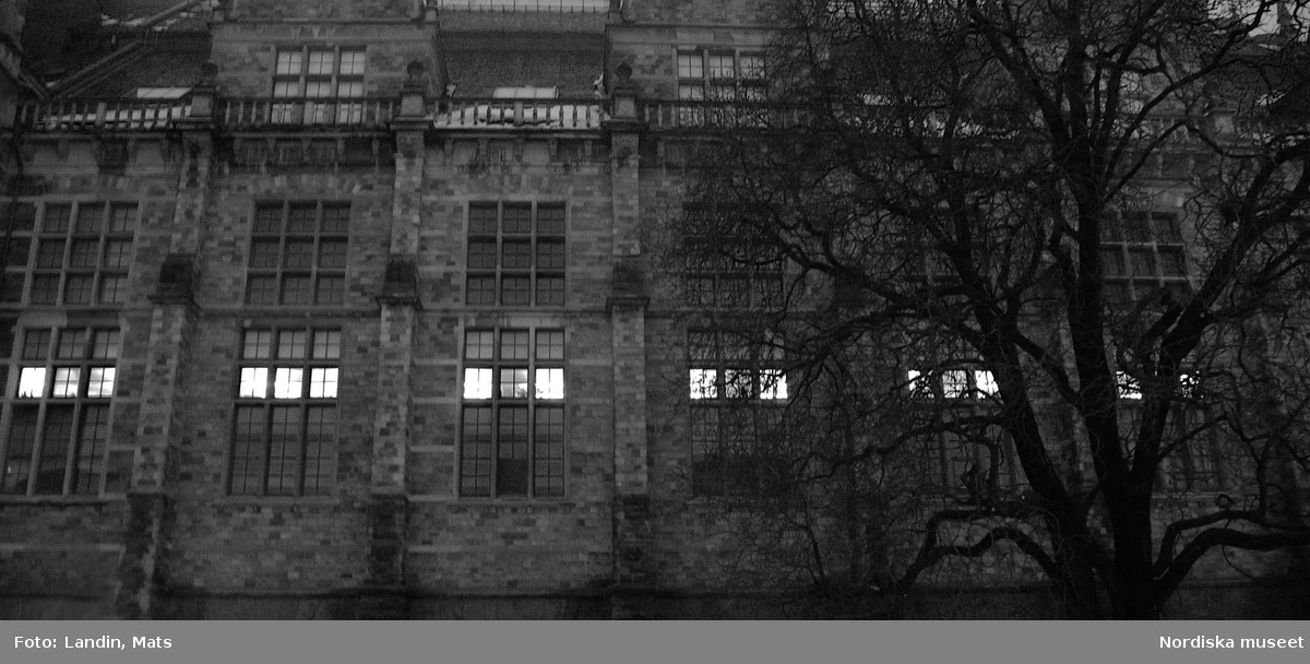 Nordiska museet. Exteriör, kvällsbild. Fönstren i de låga tjänsterummen lyser som ett pärlband när mörkret faller på.