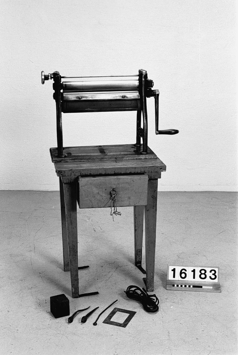 Varm-vals-apparat för snabbtorkning av blanka fotografiska kopior, på bord. Eldas med fotogenkök (Smith & Pattison, Chicago).