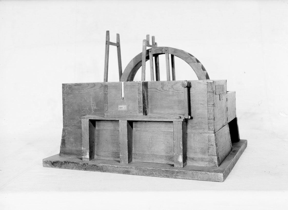 """Modell av tegelslagningsmaskin. Text på föremålet: """"XVI.B.1. E-b-5 N:o 179. E.b.1.5. Murbruks och Lerbråka""""."""