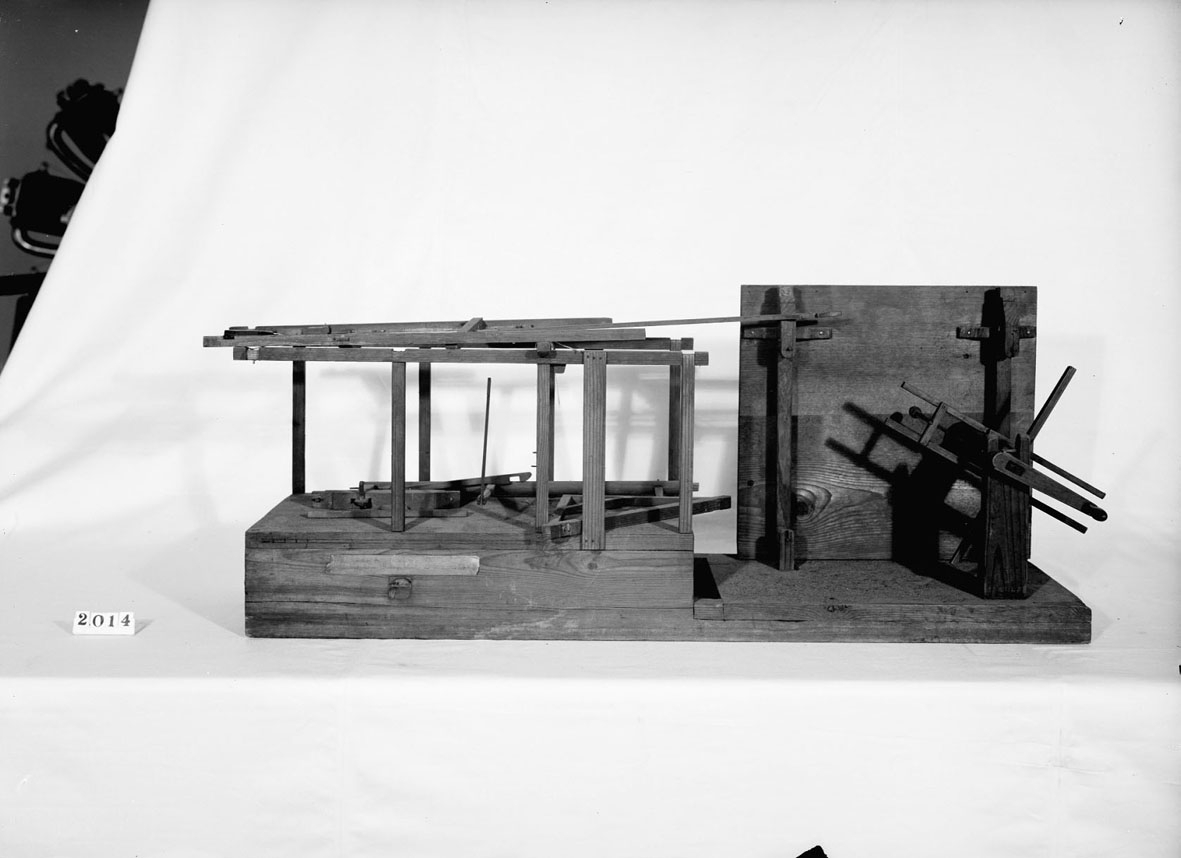 """Modell av mjölkvarnshjul kombinerat med mangel. Text på föremålet: """"XVII.E.12"""" . I Jonas Norbergs förteckning från 1779 beskrivs modellen på följande sätt: """"Modell på en rörelse, som appliceras til en Mjöhl=Qvarn, och hvarmedels man genom en kugges tilsats på hjulaxeln, kan utan hinder i maningen, tillika draga en mangel, eller annat dylikt# af undertecknad."""""""