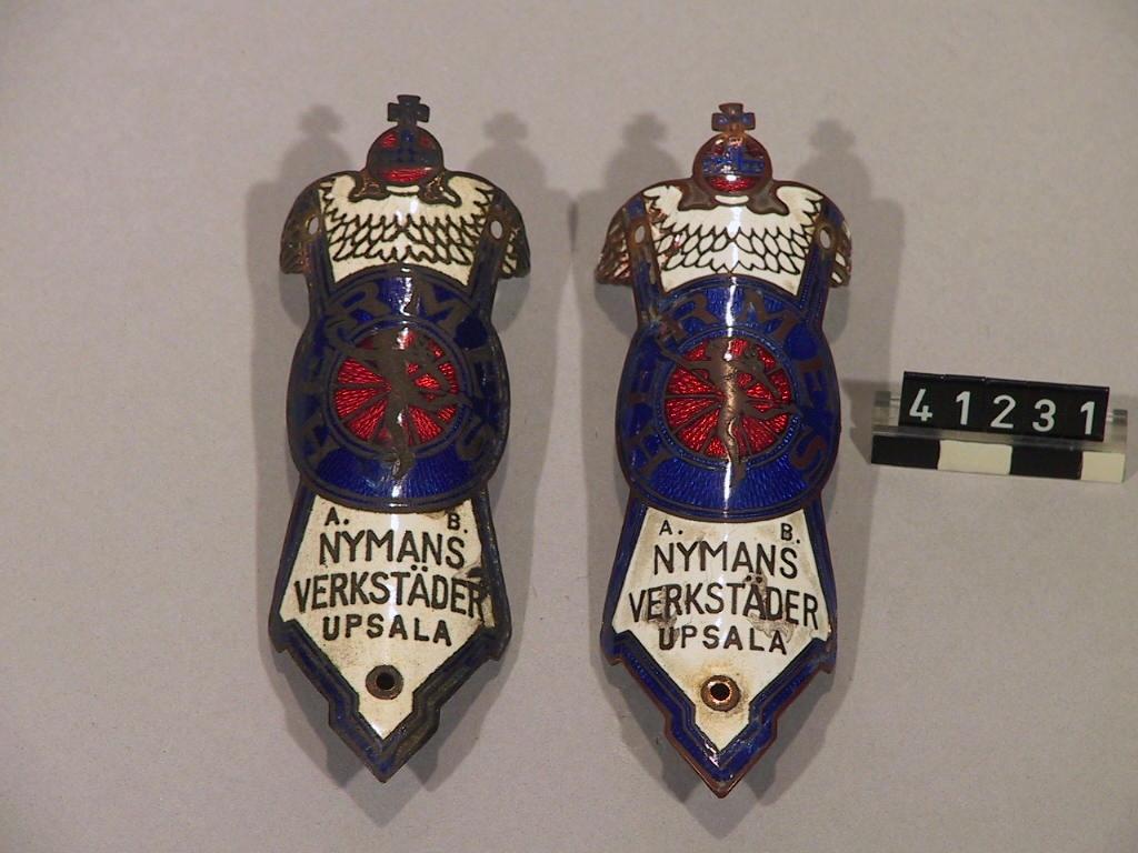 Två cykelmärken av koppar och emalj.