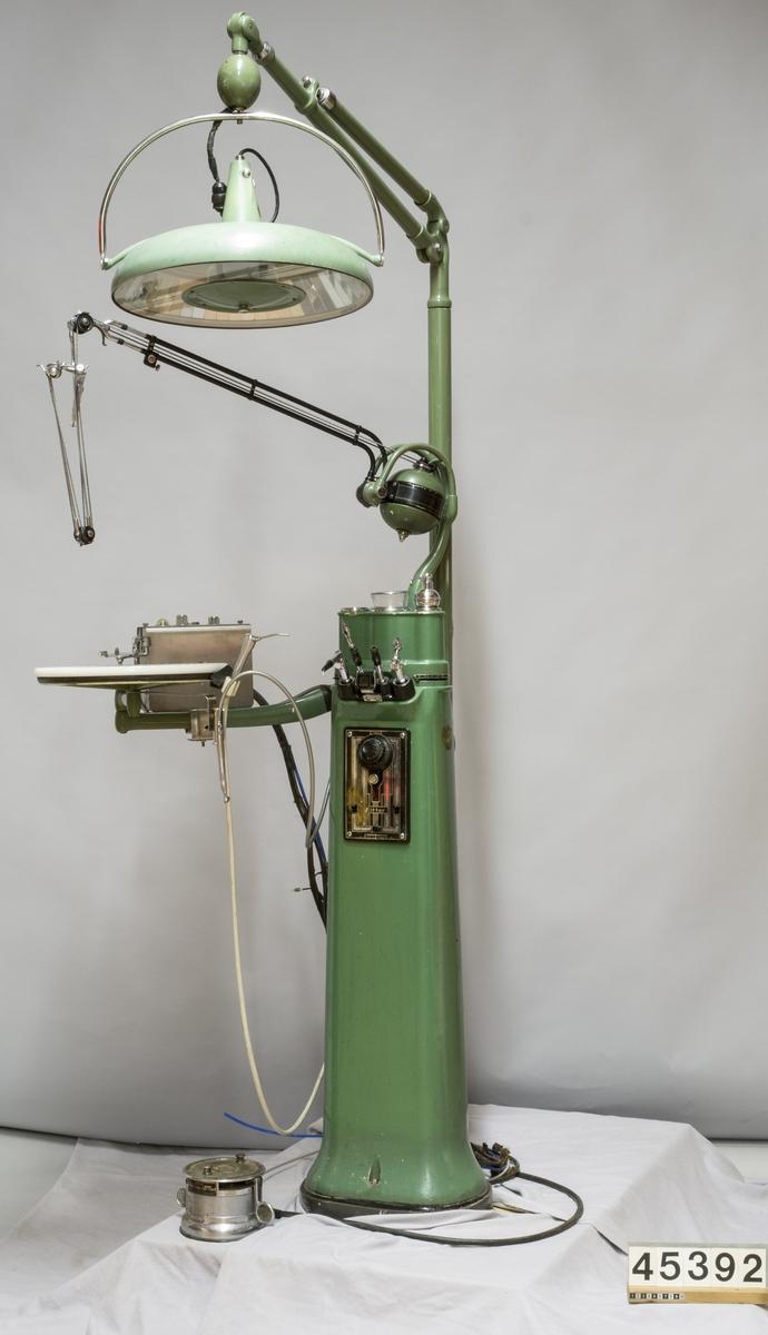 """Behandlingsstativ i grönlackerad metall med vred i bakelit och avlastningsbricka av opaliserat glas. Borrmotor med remdriven borr på länkarm, pedal för manövrering. Stativet är försett med fyra integrerade hållare för verktyg: borr, blås samt spegel med belysning. Undersökningslampa  på arm märkt Ritter: tillverkare AB Dentatus typ OGA nr 177.  Stativet är märkt med en skylt: UNIT hergestellt von Ritter A.G. Durlach-Baden B.R.P. 357698#370609#442002#446936#498076#514439#520095#533152 D.R.G.M 975317#1349505 Patente angemeldet, Patentiert in verschiedenen Länder für 250 V 5 A gleichstrom  Borrmotorn med länkarm märkt: Ritter A.G. Durlach-Baden D.R.P. 260620#263162 Likström 200/250 V 0,6 A  4000 rpm fabriksnummer D25E35021  Stativet är kompletterat med pneumatisk borr, med pedal. Tillverkare: S.S. White """"Control for operating Airotor handpiece"""" Regd in US Patent office and elsewhere Modell 13, ser 18096 220/240 V 50/60 per 1 A 25 W."""