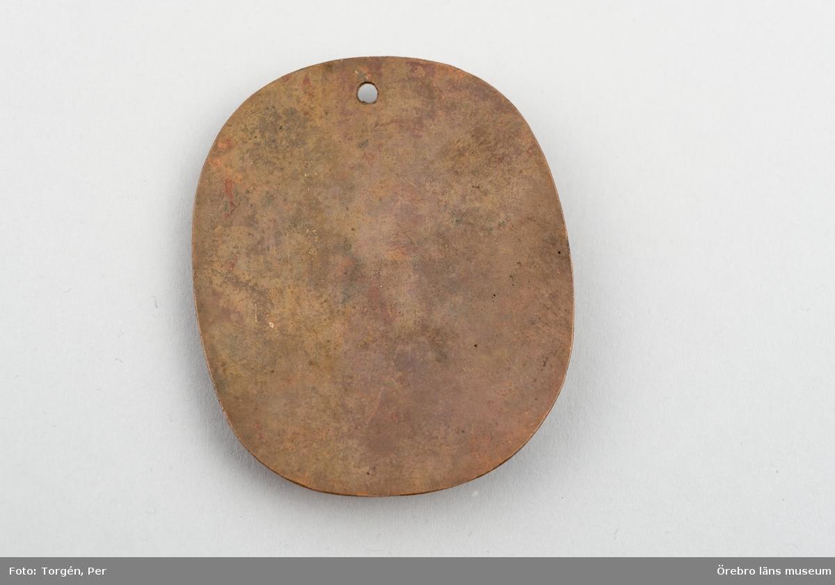 Koleraamulett av koppar, mindre, rundade hörn. Att bära inpå kroppen till skydd mot kolera.Ett utstansat hål på ena kortsidan.Neg.nr. 1590/86