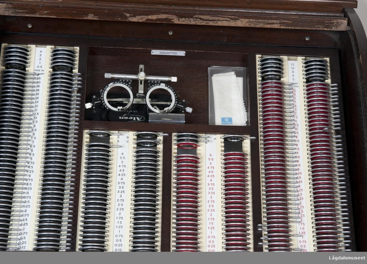 """Brillekasse for synsprøve i mørkbeiset/lakket trekasse. Kassen består av et bakrom som er formet og utstyrt som en lyskasse med lysrør og hvit metallbakgrunn. Som llokk til lyskassa er det en trekasse/brett med fire rom . Tre av rommene er igjen """"innredet"""" for oppbevaring av prøveglass til briller. Det fjerde rommet er til oppbevaring av småting. I dette tilfellet oppbevares en stk prøvebrille (LK2013-0015a), en plastbrikke (LK2013-0015b) og et futeral med pusseklut (LK2013-0015c).  Rommene 1-3 inneholder tilsammen 283 stk prøveglass (LK2013-0015d), hvorav 155 stk har sort omramming og 128 rød omramming.  Brillekassen har et lokk som er av typen jalusi, formet som en kvart sirkel sett fra enden.  Inne i rommet for småting er det festet et hvitt skilt som er festet til treverket med 2 små stifter. På skiltet står det trykt """"MADE TO BRITISH STANDARD 3162""""."""