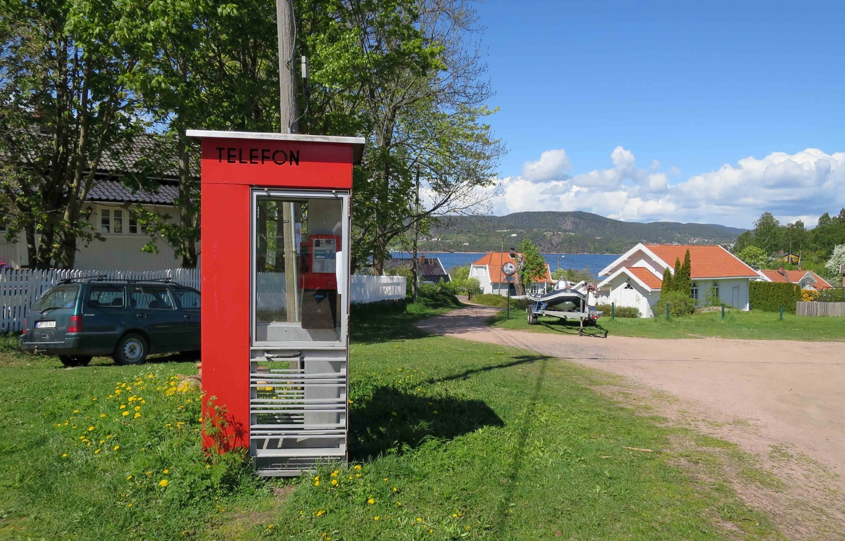 Denne telefonkiosken står på Rødtangen, Holmsbu i Hurum, og er en av de 100 verna telefonkioskene rundt om i landet. De røde telefonkioskene ble laget av hovedverkstedet til Telenor (Telegrafverket, Televerket) Målene er så å si uforandret.  Vi har dessverre ikke hatt kapasitet til å gjøre grundige mål av hver enkelt kiosk som er vernet.  Blant annet er vekten og høyden på døra endret fra tegningene til hovedverkstedet fra 1933. Målene fra 1933 var: Høyde 2500 mm + sokkel på ca 70 mm Grunnflate 1000x1000 mm. Vekt 850 kg. Mange av oss har minner knyttet til den lille røde bygningen. Historien om telefonkiosken er på mange måter historien om oss.  Derfor ble 100 av de røde telefonkioskene rundt om i landet vernet i 1997. Dette er en av dem.