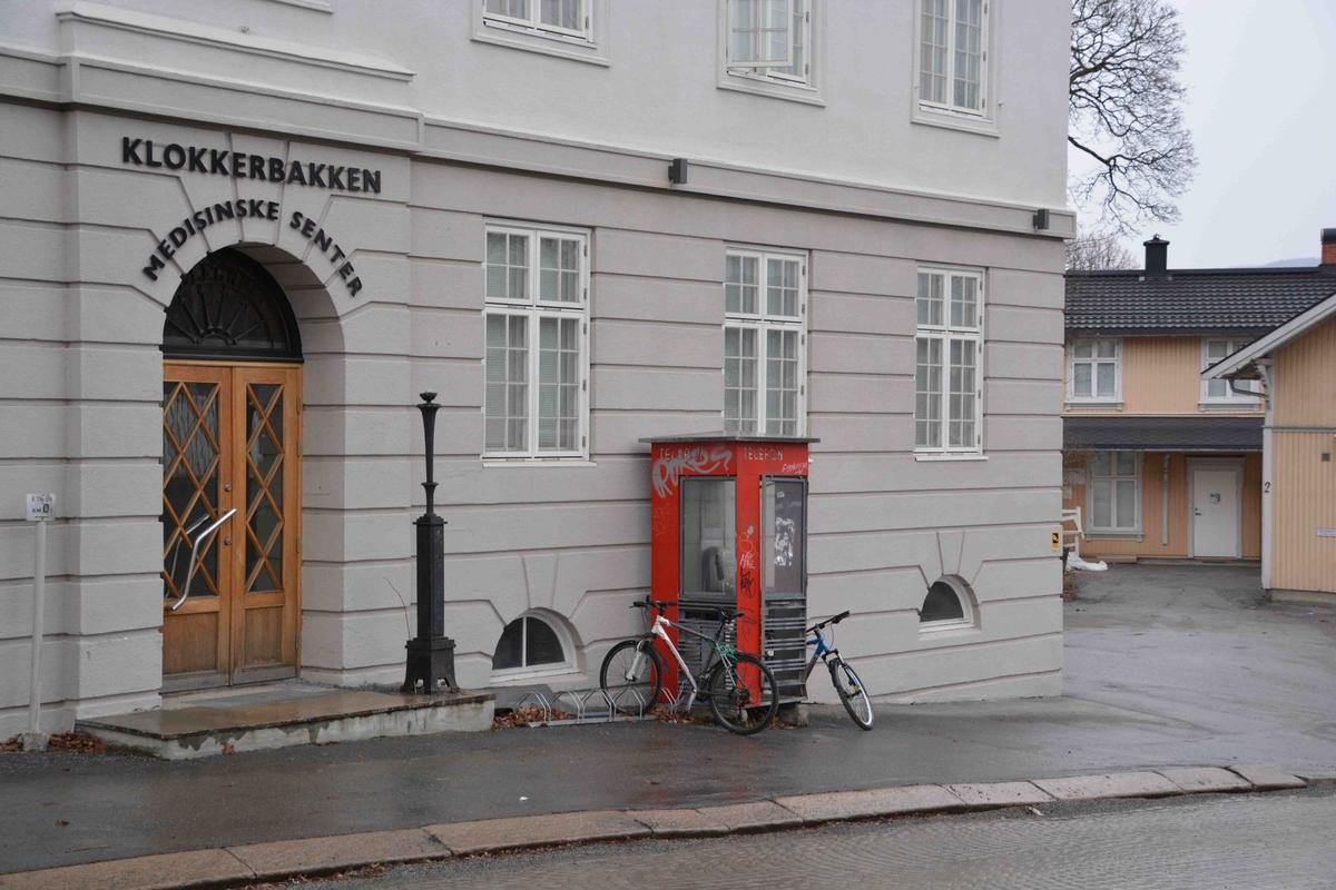 Denne telefonkiosken står i Myntgata 4 i Kongsberg, og er en av de 100 verna telefonkioskene rundt om i Norge. De røde telefonkioskene ble laget av hovedverkstedet til Telenor (Telegrafverket, Televerket) Målene er så å si uforandret.  Vi har dessverre ikke hatt kapasitet til å gjøre grundige mål av hver enkelt kiosk som er vernet.  Blant annet er vekten og høyden på døra endret fra tegningene til hovedverkstedet fra 1933. Målene fra 1933 var: Høyde 2500 mm + sokkel på ca 70 mm Grunnflate 1000x1000 mm. Vekt 850 kg. Mange av oss har minner knyttet til den lille røde bygningen. Historien om telefonkiosken er på mange måter historien om oss.  Derfor ble 100 av de røde telefonkioskene rundt om i landet vernet i 1997. Dette er en av dem.