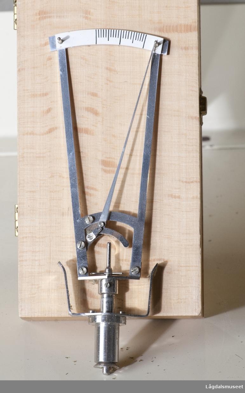 Måleinstrument i rustfritt stål, til å måle trykk på øyet. Målet har på den ene enden et buet mål hvor det er avmerket to centimeter, På den andre siden er det et rundt håndtak til å justere målet. Mellom håndtak og målgradering er det en spiss pendel.