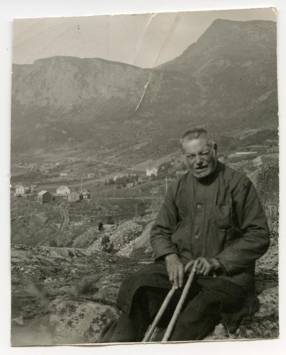 Portrett av en eldre mann sittende på noen steiner med hus i bakgrunnen. Mannen holder på to stokker.