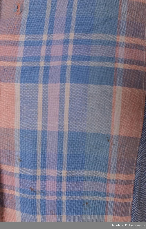 Sommerkjole, Blått/Hvitt toskaftvevet bomullstoff med krage, ermlinninger og belegg på forkantene av rutet blått/hvitt/lyserødt bomullstoff. overdel med lage ermer rynket til linning. knapping foran med grå metallknapper. Skjørt av 6 Skrådde bredder med splitt med trykknapper på venstre side foran. Ltt fillet i armhulene. Maskinsydd