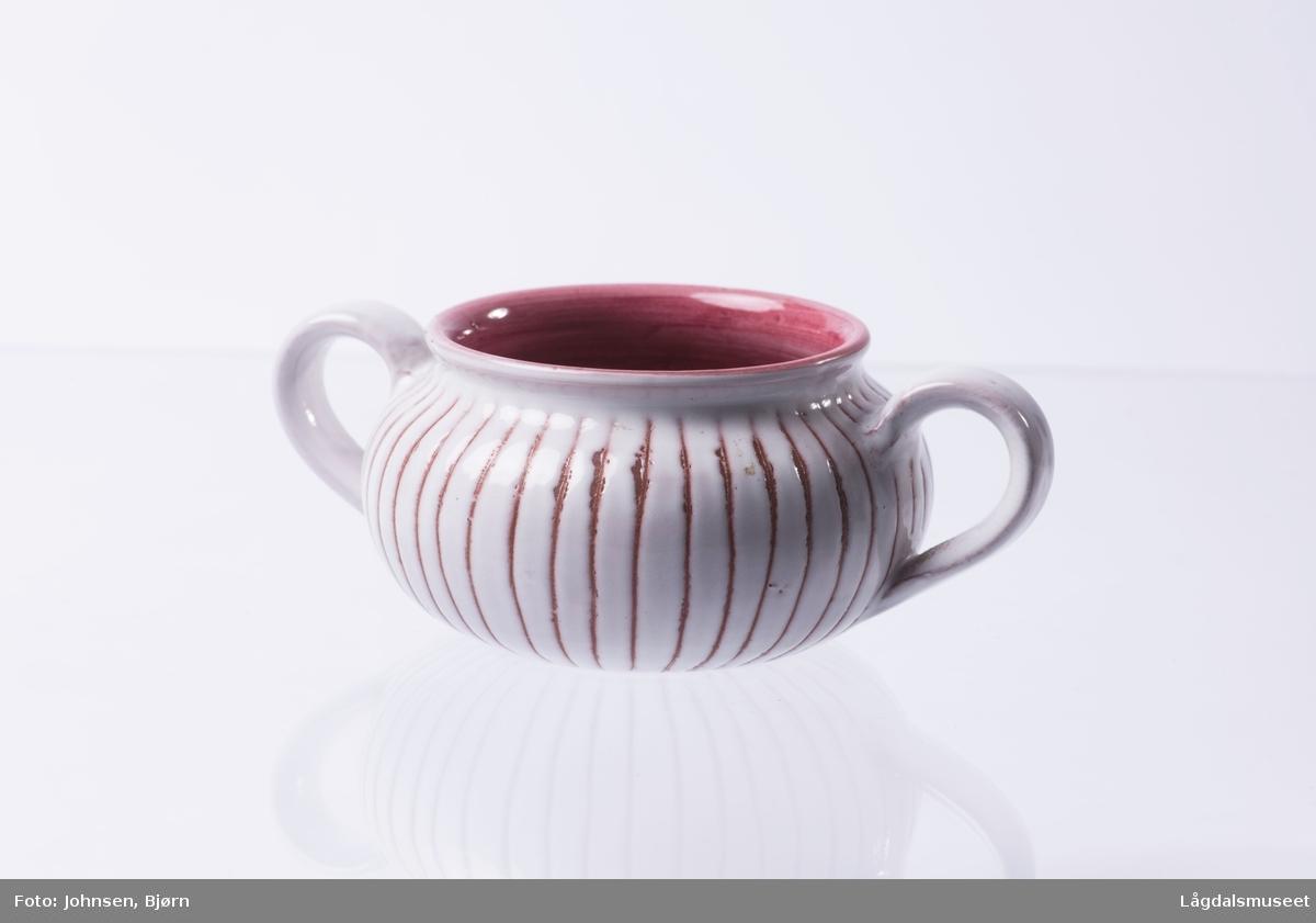 Dekorert med hvit og rosa begitning i striper. De hvite stripene er bredest.