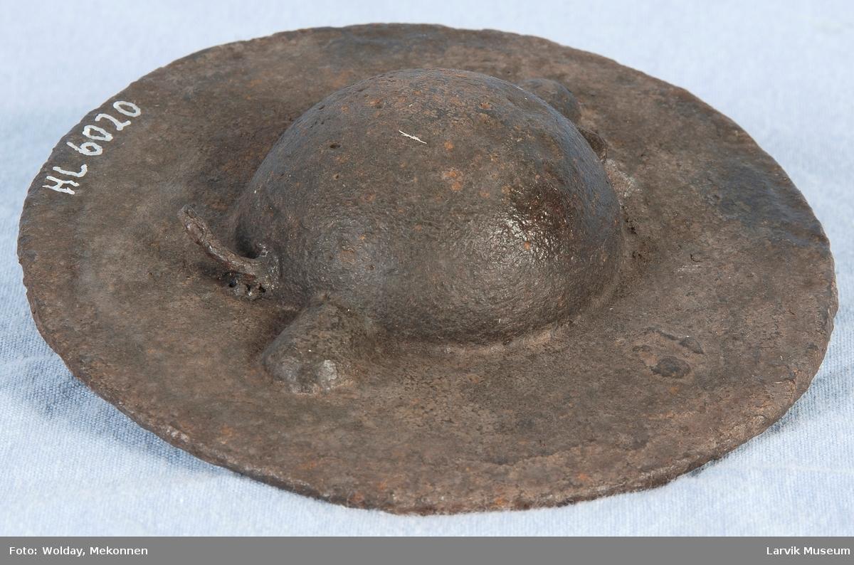 Rundt lokk til jernovn, ant. etasjeovn, nedsunket håndtak/grep danner en kule på baksiden