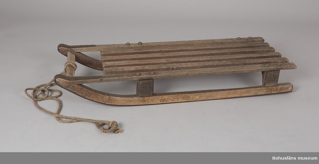 Kälke eller bomma använd för isfiske på Byfjorden under 1900-talets första hälft. Tillverkad av en snickare i Uddevalla, som tog 5 riksdaler för den. Även brukad av barn för lek. För upplysningar om ägarna, Gunnar och Greta Karlsson, se UM018527. Gåvan omfattar UM022759 - UM022779.