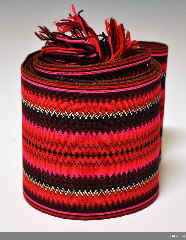 """Rektangulært belte til Beltestakken i fargene rødt, vinrødt, cyklamen, svart og hvitt. Belte er vevd i brikkevevteknikk og er av ull. Lange frynser av renningen i  den ene enden og  en """"kanal """"laget av renningen i den andre enden."""